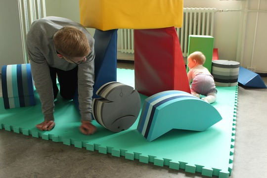 Far og baby kravler på gulvet med legeredskaber