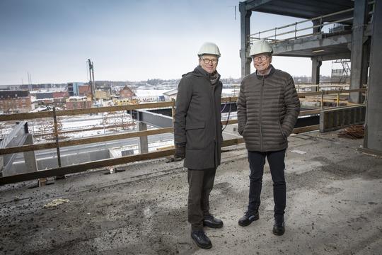 Projektchef Lars Autrup fra Realdania (t.v.) sammen med borgmester Ulrik Wilbek på byggepladsen ved Midtbyens Gymnasium i Viborg Baneby. I baggrunden ses det område, hvor Hærvejsbroen begynder at tage form i 2018. Foto: Flemming Jeppesen.