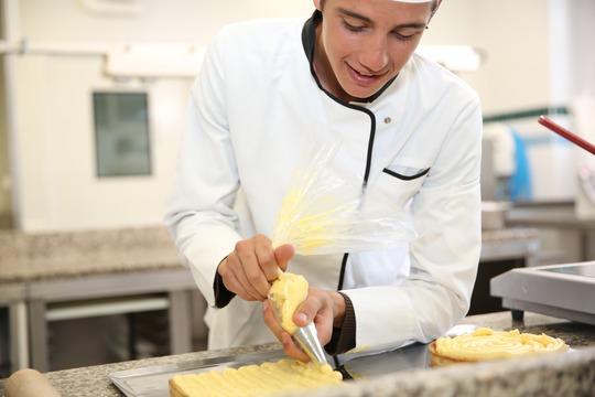 Ung person bager i et køkken