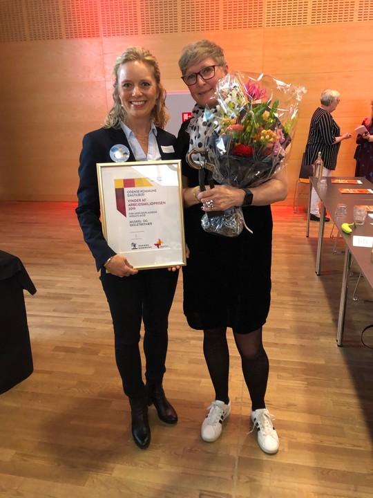 Karen Louise Reeh og Lotte Sanner Kjeldsen fremviser Arbejdsmiljøprisen 2019