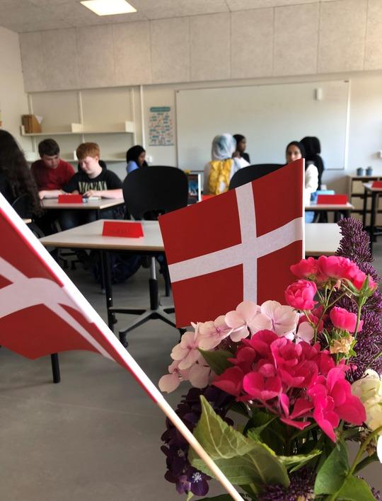 Flag og blomster i klasseværelse med elever i baggrund